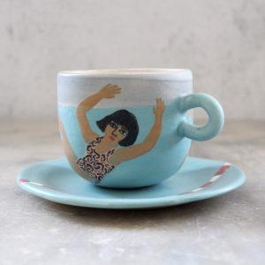 Ensemble tasse et sous-tasse en grès illustrée au pinceau avec des engibes. Thème piscine, nageuse et eaux turquoises
