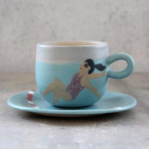 Ensemble tasse et sous-tasse en grès illustrée à la main aux engobe. Thème jeune nageuse et eaux turquoises