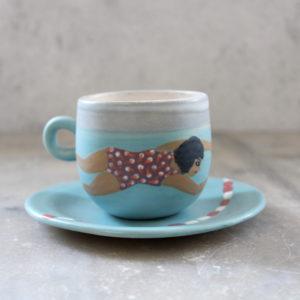 Ensemble tasse et sous-tasse en grès. Illustrée à la main avec pour thème la piscine et une nageuse.
