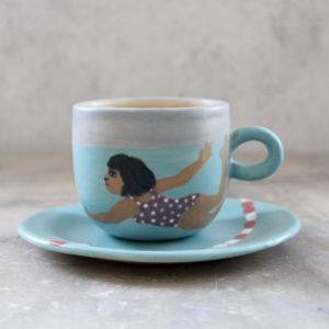 ensemble tasse et sous-tasse en grès illustrée avec des engobes. Thème piscine,nageuses et eau turquoise