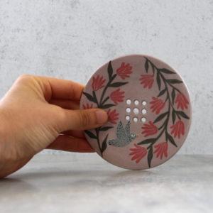 porte savon artisanal en grès décoré à la main. porte savon violet à fleurs rouge avec oiseau gris.