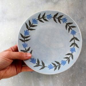 assiette à dessert artisanale en grès couleur bleu ciel avec frise de fleurs bleues