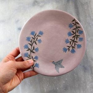 assiette artisanale en grès décorée à la main. Illustration oiseau avec fleurs bleues sur fond violet.